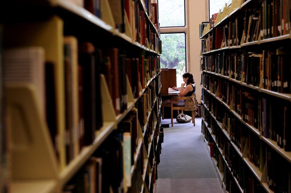 فتاة تذاكر دروسها في مكتبة
