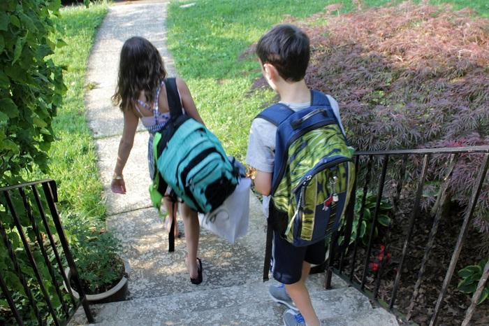 أطفال يحملون حقائب ثقيلة