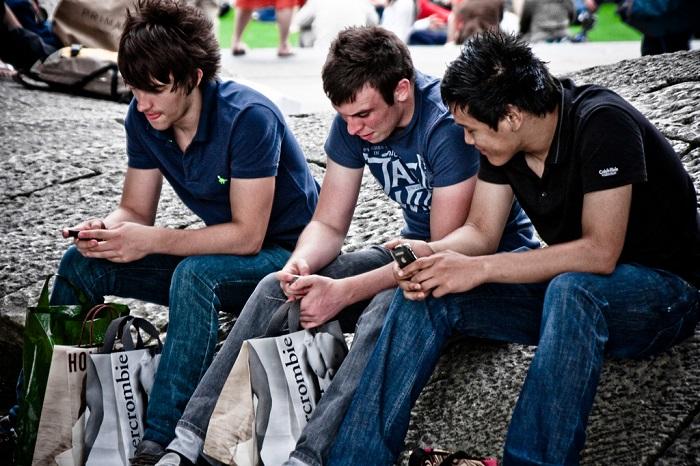 شباب جلوس ينظرون في هواتفهم