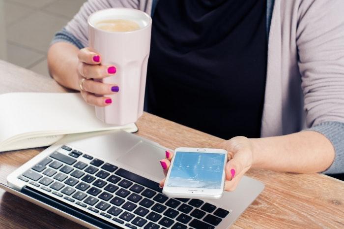 فتاة تستخدم الموبايل وتشرب قهوة