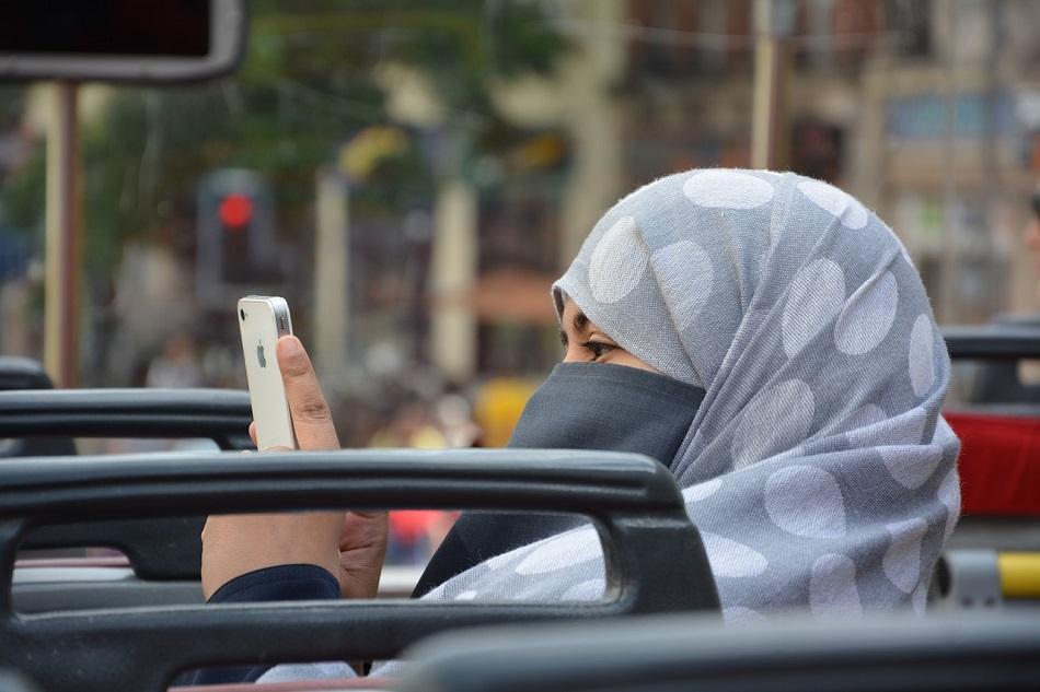 سيدة ترتدي الحجاب تمسك هاتف محمول