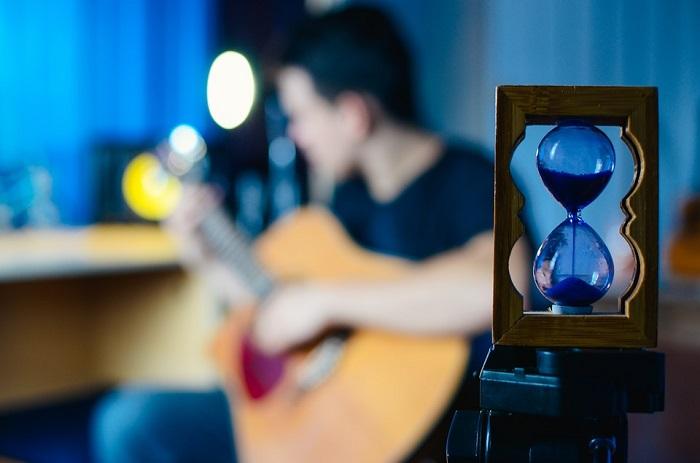 رجل يعزف على الجيتار وامامه ساعة رملية