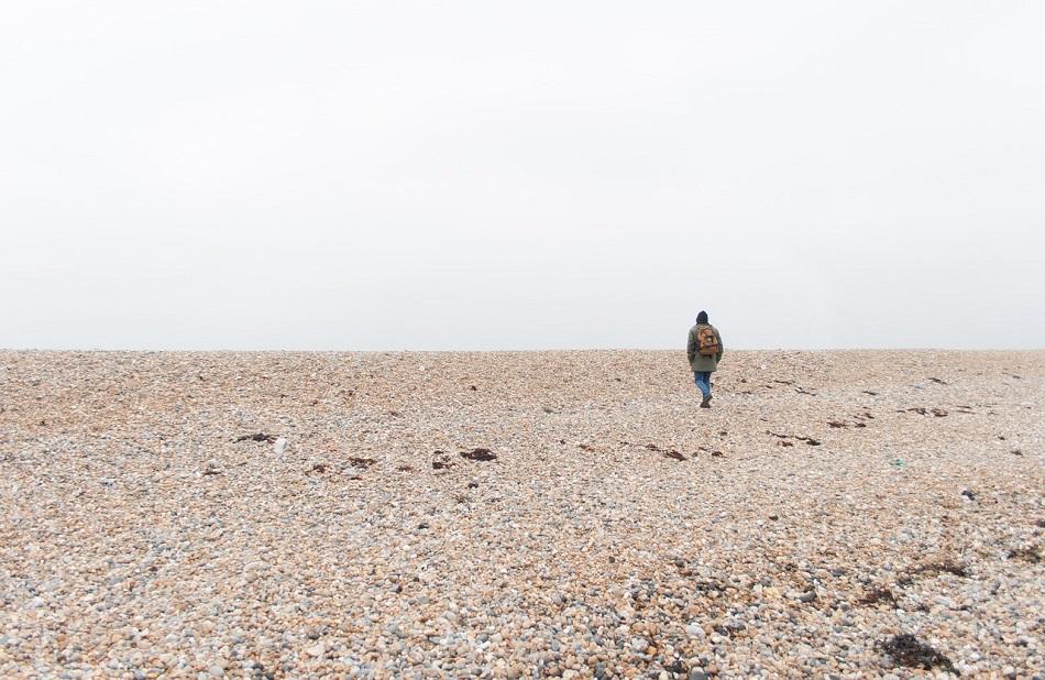 شخص يسير وحيدا على الشاطئ