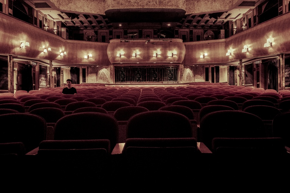 شاب يجلس وحيدا في قاعة سينما