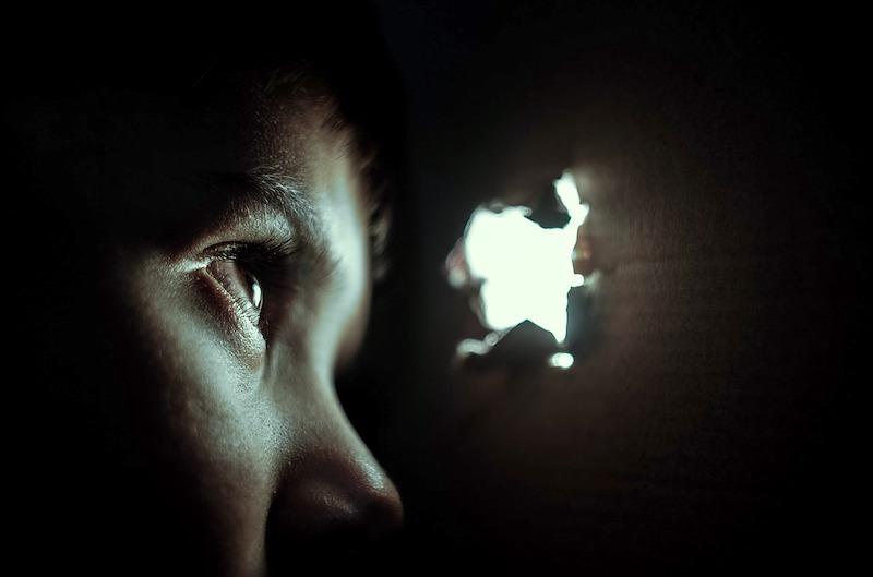 طفل خائف يختبئ وينظر من ثقب صغير