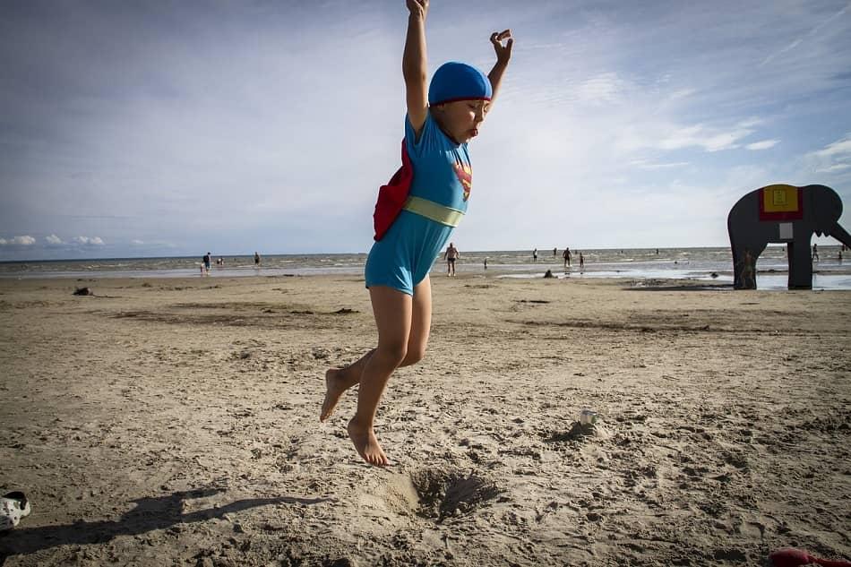 طفل يلبس زي سوبرمان ويقفز على شاطئ البحر