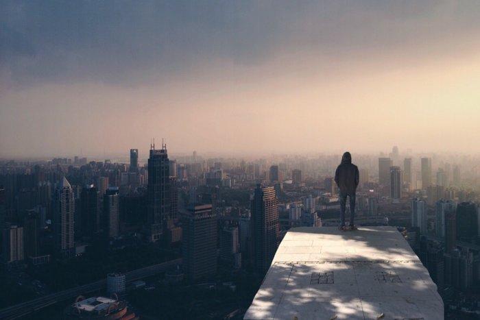 شاب يقف وحيدًا على قمة مبنى وينظر إلى المدينة