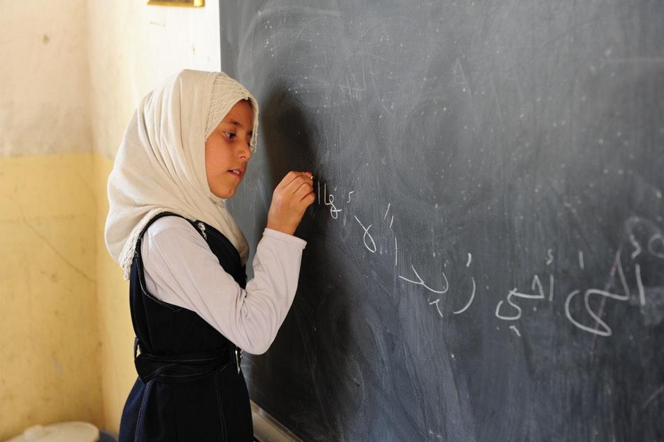 فتاة عربية تكتب على السبورة