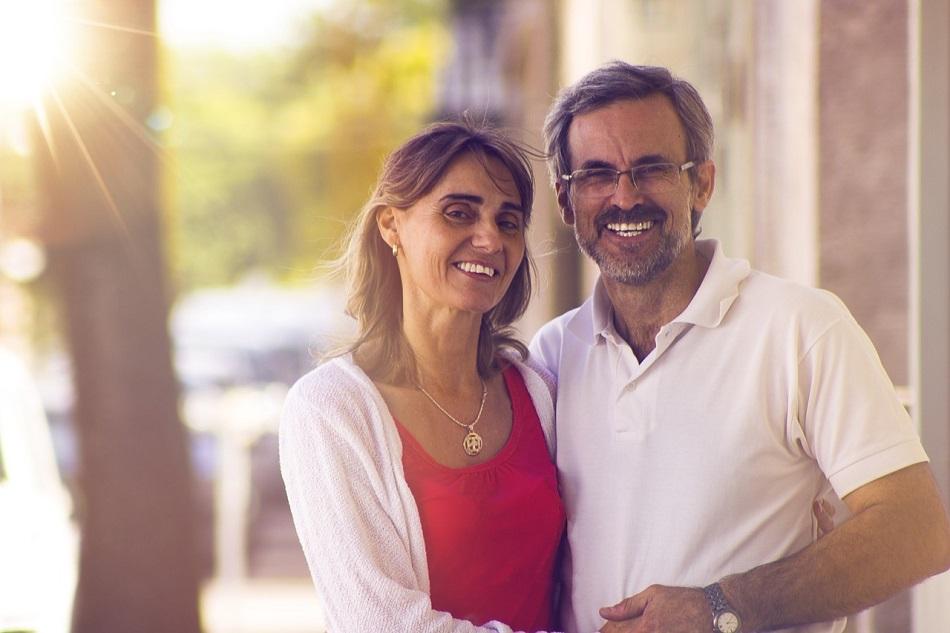 زوج وزوجته يبتسمان وهما يحتضنان بعضهما