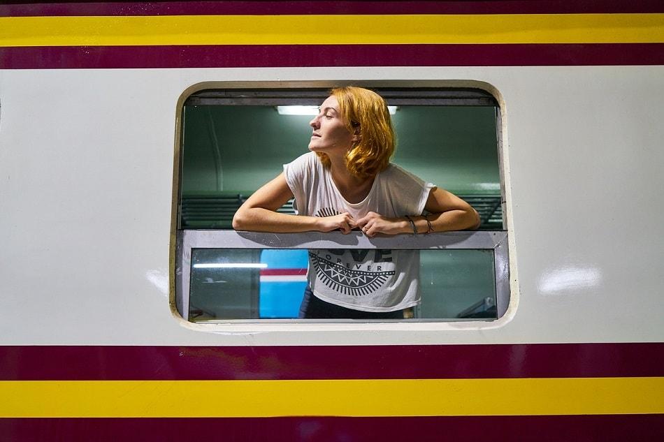 فتاة تخرج من شباك قطار وتبتسم بسعادة