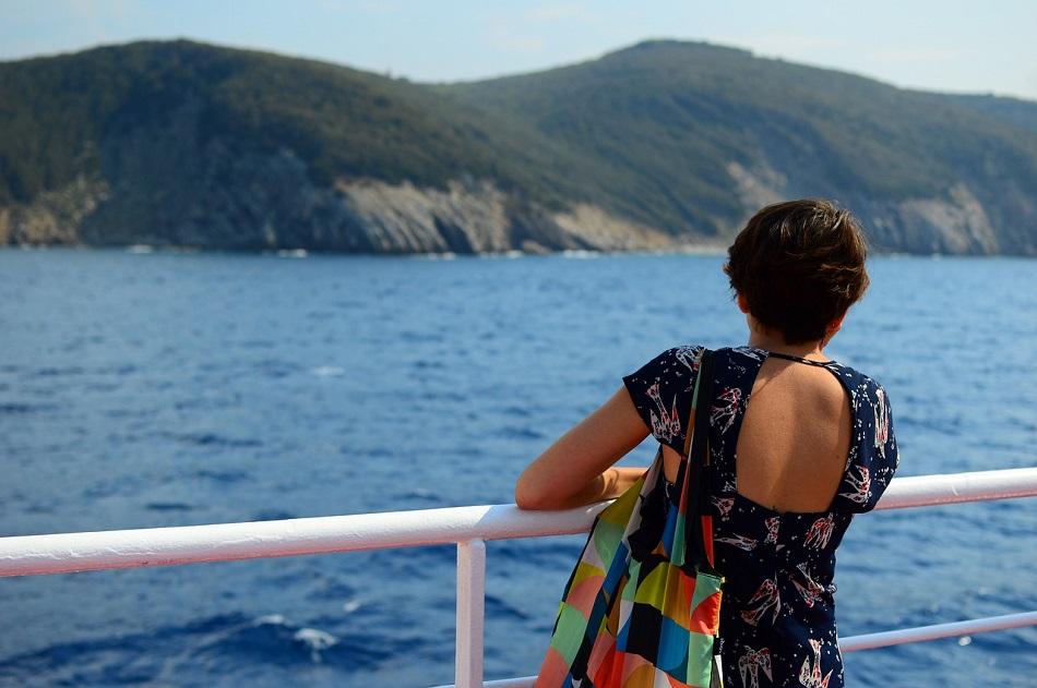 فتاة وحيدة تستند إلى سور سفينة في البحر