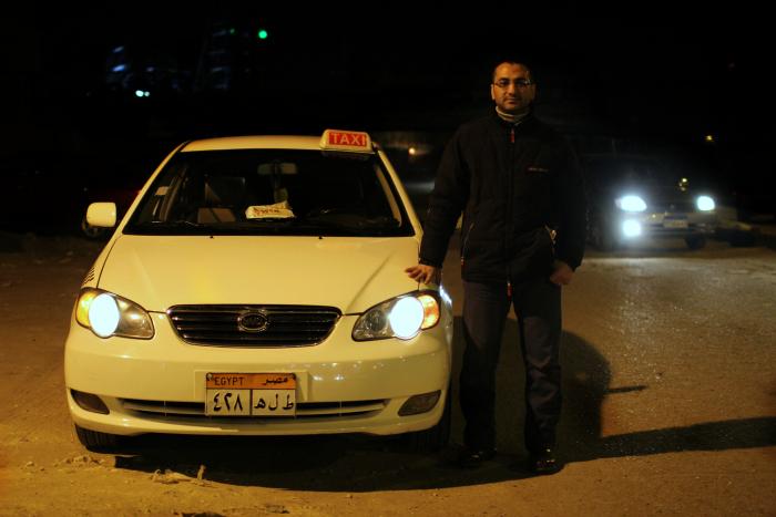 رجل يقف أمام التاكسي الخاص به