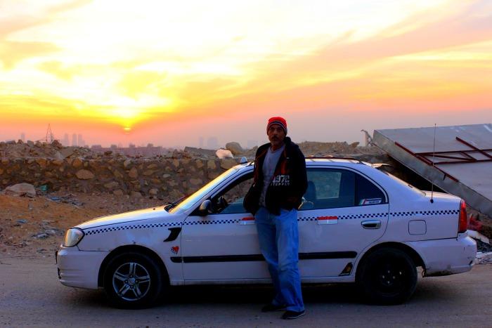 رجل يقف أمام التاكسي به وخلفه الغروب