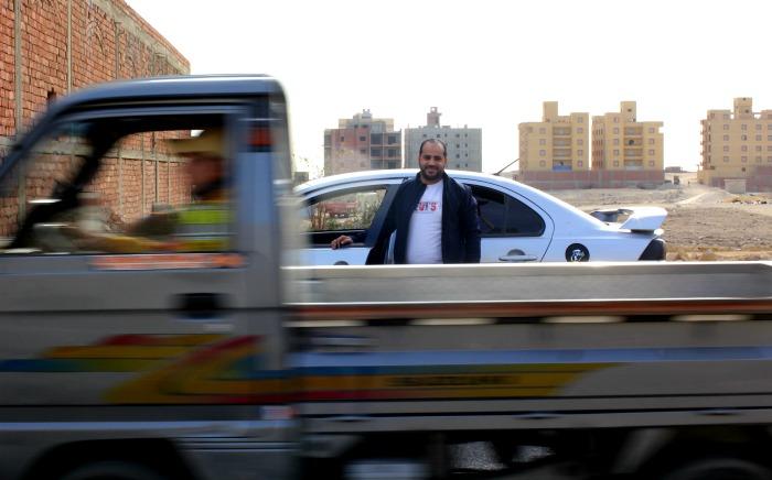 رجل يقف أمام سيارة كريم