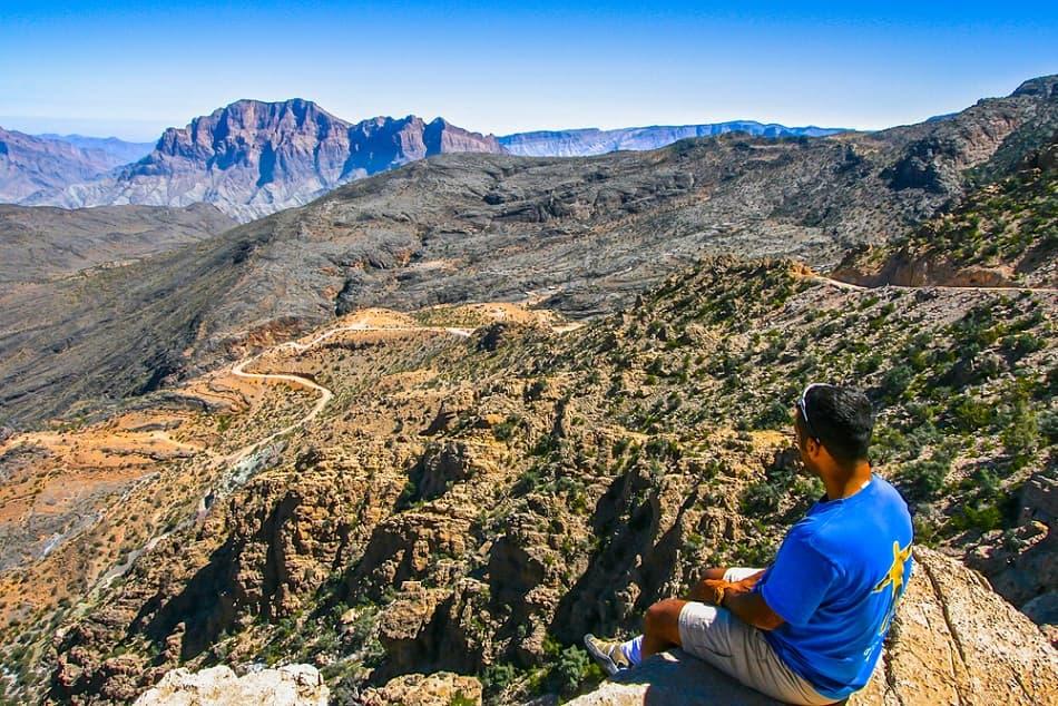 شاب يجلس على قمة جبل في عمان
