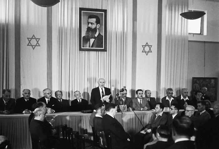 ديفيد بن جوريون يعلن قيام إسرائيل وفوقه صورة هرتزل