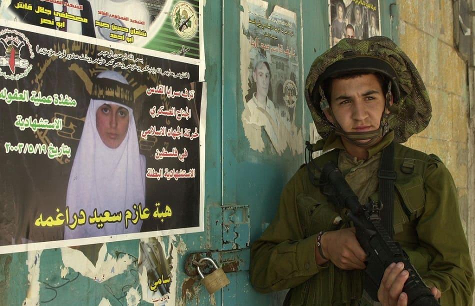 جندي إسرائيلي يقف إلى جوار صورة شهيدة فلسطينية