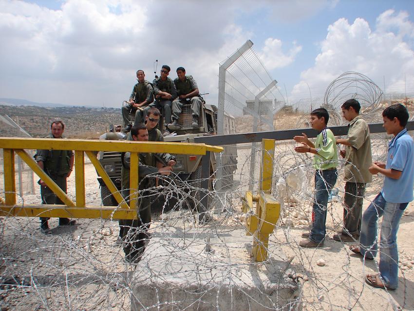 جنود إسرائيليون مع أطفال فلسطينيين على حاجز