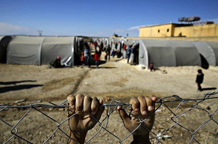 لاجئ يتشبث بسور من السلك يفصل المخيم عمَّا وراءه