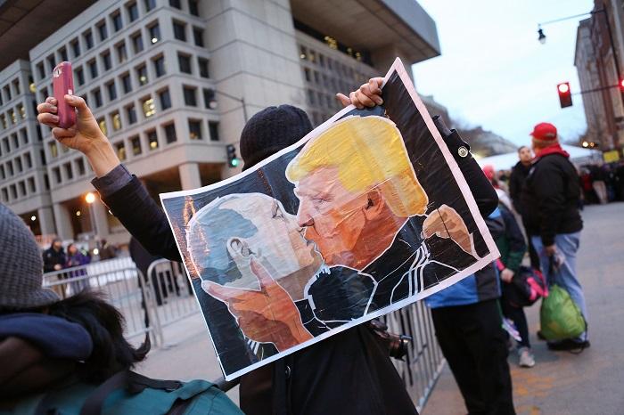 متظاهر يحمل لافتة لترامب وبوتين يقبلان بعض
