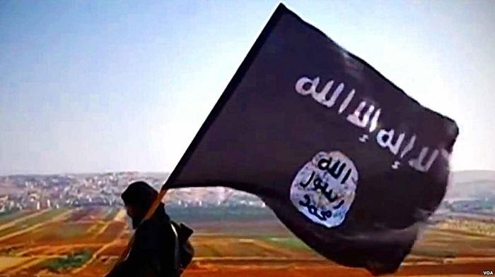 مقاتل من داعش يحمل علم لا إله إلا الله