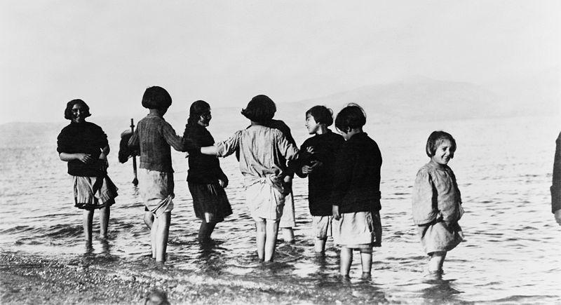 أيتام من اللاجئين يلعبون في البحر