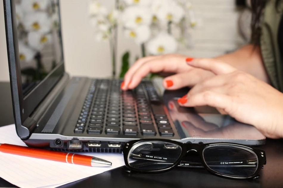 سيدة تكتب على جهاز كمبيوتر