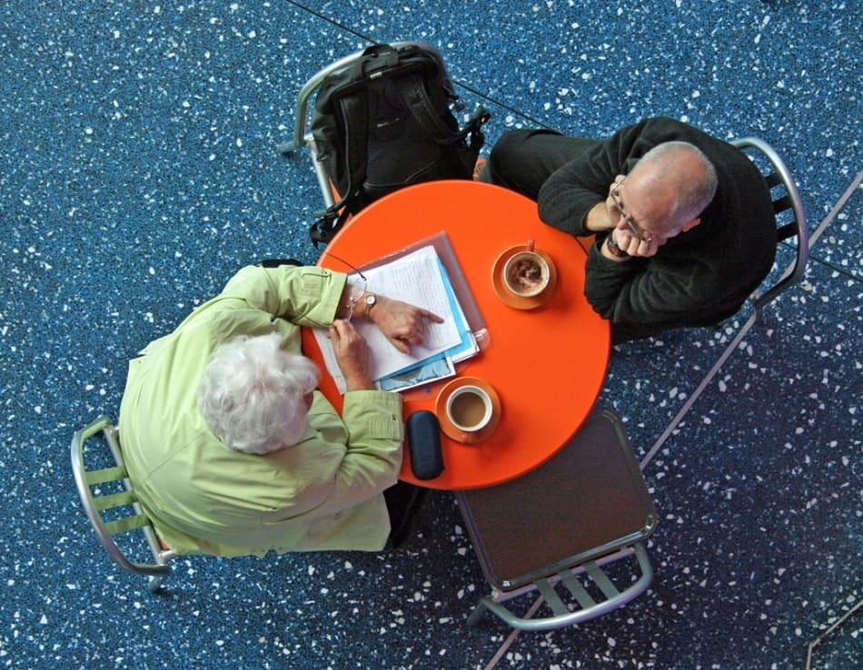رجل عجوز وامرأة عجوز يتحدثان على طاولة مقهى