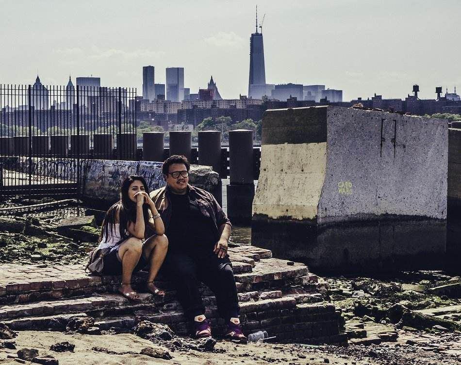 شاب وفتاة يجلسان إلى جوار سور متهدم