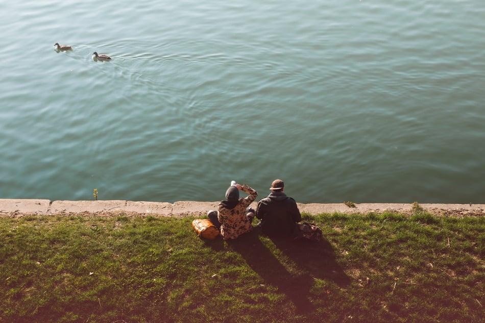 شاب وفتاة يجلسان على شاطئ النهر