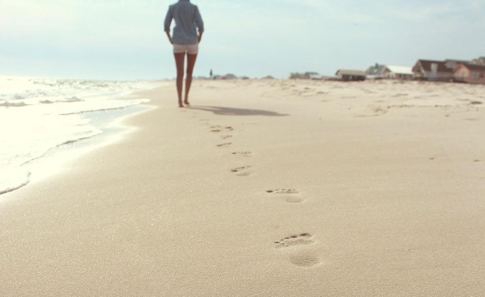 فتاة تمشي وحيدة على الشاطئ وتترك آثار قدميها