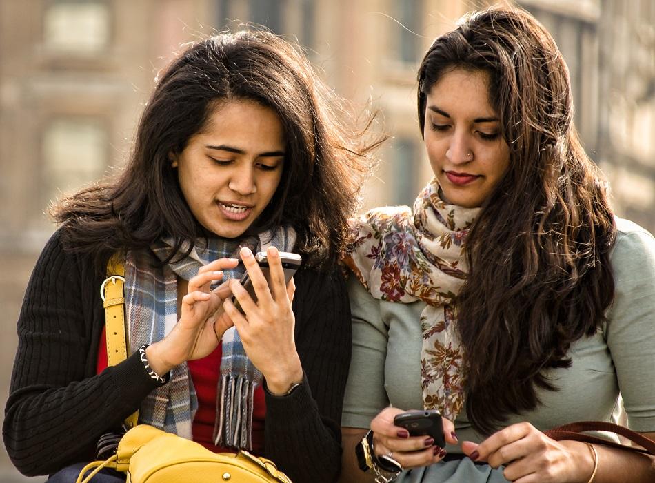 فتاتان تبعثان رسالة على الموبايل