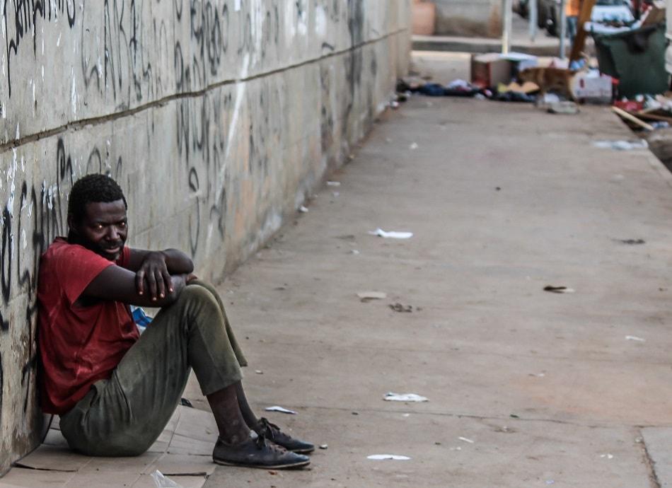 رجل أسود فقير يجلس على الرصيف وينظر بعدوانية