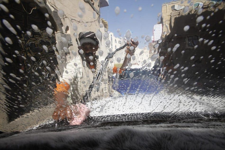 رجل فقير يغسل زجاج سيارة