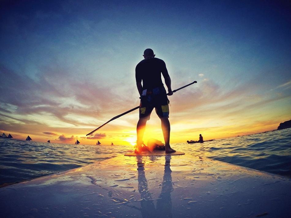 شاب يمارس رياضة التزحلق على الماء وقت الغروب