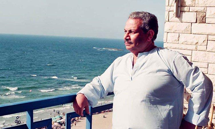 كاتب السيناريو أسامة أنور عكاشة يقف في شرفة شقة في الإسكندرية