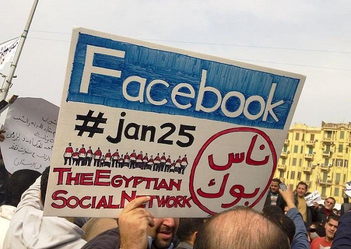 متظاهر يحمل لافتة أثناء ثورة 25 يناير عليها كلمة فيس بوك