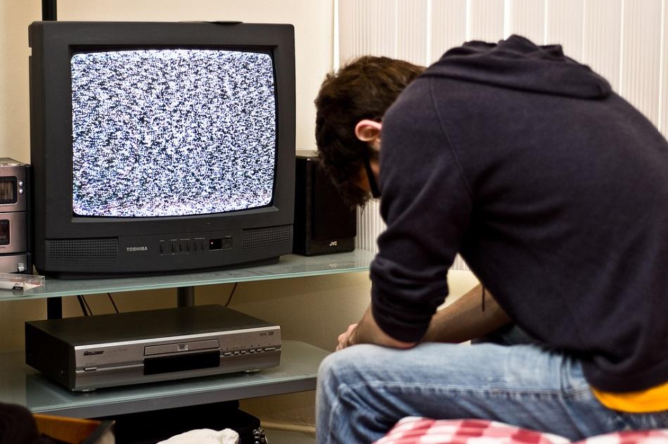 شاب مكتئب يجلس أمام التليفزيون