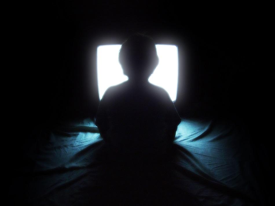 طفل يجلس في الظلام أمام التليفزينن