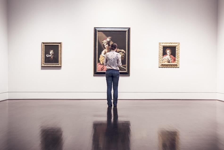 فتاة تتأمل لوحة في متحف