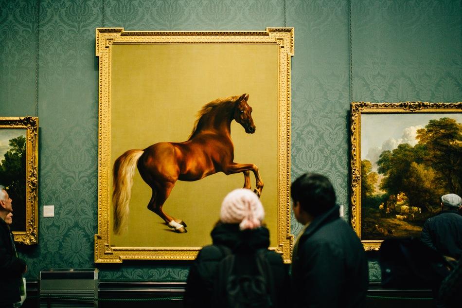 شاب وفتاة ينظران إلى لوحة حصان